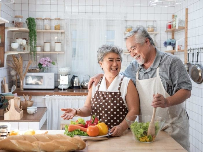 Happy senior couple cooking with fresh vegetables